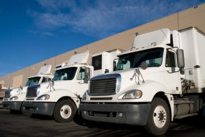 Three white long haul Semi trucks parked outside a shippping and receiving distribution warehouse.